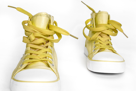 top view to golden nice tender new sneakers with white foot and wide open shoelaces on white. modern stylish sneakers isolated on white background. new high keds for woman or man stay strong