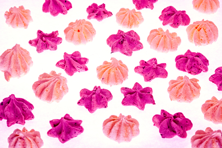 Colorful meringues on white. Many sweet zephyrs pattern background. Trendy top view dessert image. Bakery products top view. Colorful cookies background. stars and flowers meringues lay one by one.