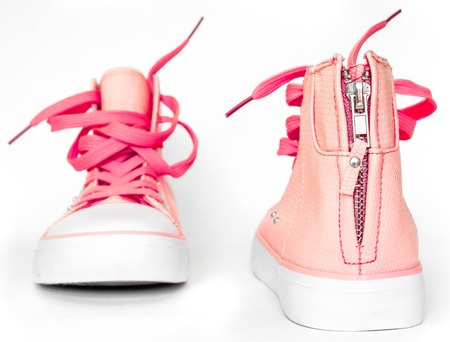 front and back of pink nice tender new sneakers with white foot and wide open shoelaces on white. modern stylish sneakers isolated on white background. new high keds for woman or man stay strong
