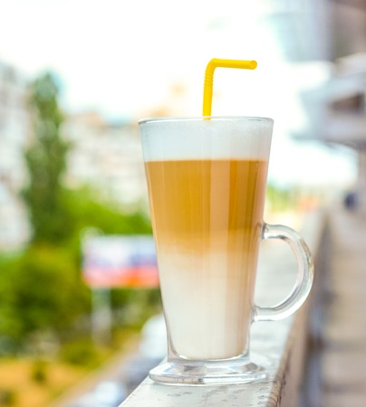 strong high clean glass cup with latte against blue sky with white clouds. layer of milk, coffee and milk foam in classic coffee latte cup with strong yellow cocktail tube as drink full of energy.