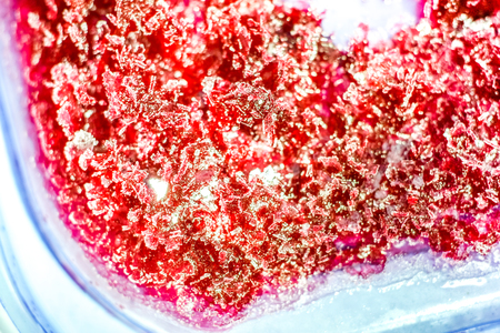 big and small chaotic crystals as background. The frozen refrigerated black currant jam in a plastic container. Isolated with path top view macro