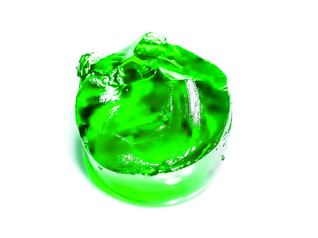 big round peace of green apple jelly against white background side top view. Homemade Gelatin jelly Dessert in a Bowl