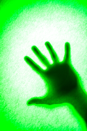 Mans hand as actor of shadow theatre. Hands shadow as figure of Shadow hands of the Man behind frosted glass. Blurry hand abstraction. Halloween background. green and white picture Stock Photo
