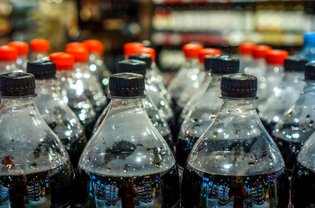 strong rows with clean plastic bottles with black sweet liquid. big army of bottles with red and black covers in grosery shop. plastic bottles with soft drinks background
