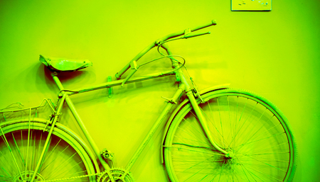 close up of bicycle as decoration on the wall. old painted bicycle attached to the wall in art office toned to green color. vintage bicycle on decorative color wall