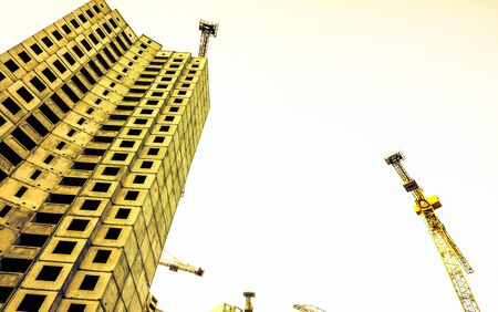high building building without windows with building cranes near