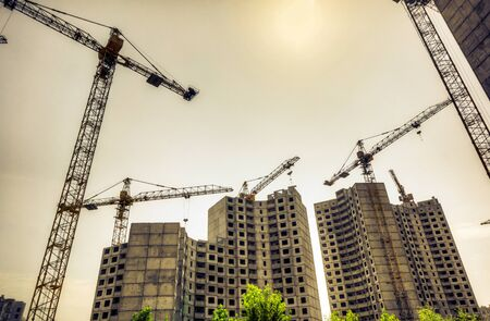sunset sky above building cranes near of a multi-storey building under construction, new houses for many families, babies and new life, building multi-storey building as symbol of hope to better life Imagens