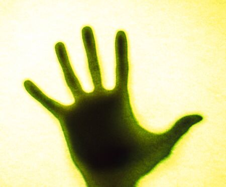 Mans hand as actor of shadow theatre. Hands shadow as figure of Shadow hands of the Man behind frosted glass. Blurry hand abstraction. Halloween background. Black and white picture