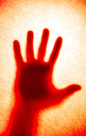 red bloody hand shadow on orange background. strange bloody hand
