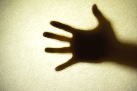Mans hand as actor of shadow theatre. Hand's shadow as figure of Shadow hands of the Man behind frosted glass. Blurry hand abstraction. Halloween background. Black and white picture Archivio Fotografico