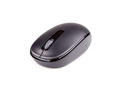 Black wireless mouse on a white surface. Computer mouse isolated on white background.