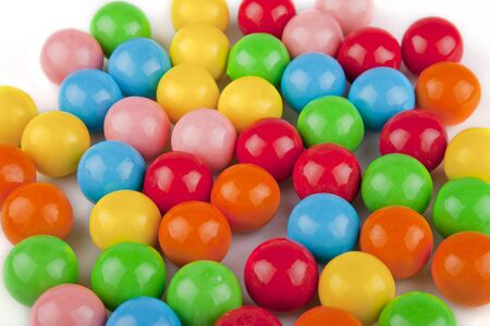 multicolored gumballs: Multicolored gumballs on a white surface. Bubble gums isolated on white background.