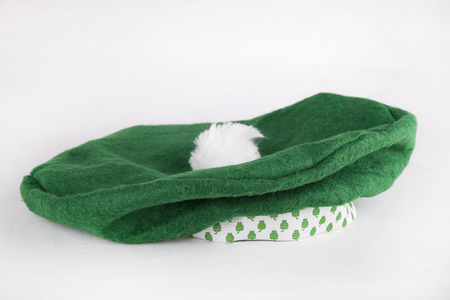 Bright green St-Patricks beret on a white surface. St-Paddy hat with shamrocks isolated on white background.