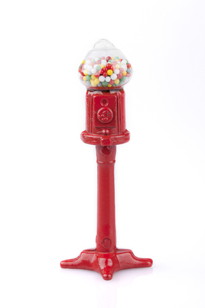 multicolored gumballs: Miniature vintage red bubblegum machine on a pedestal on a white surface. Bubblegum machine isolated on white background.