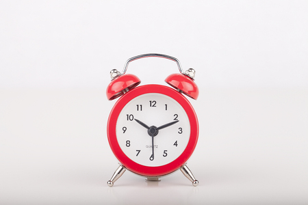 Replica of a vintage red bell alarm clock on a white surface. Alarm clock isolated on white background.