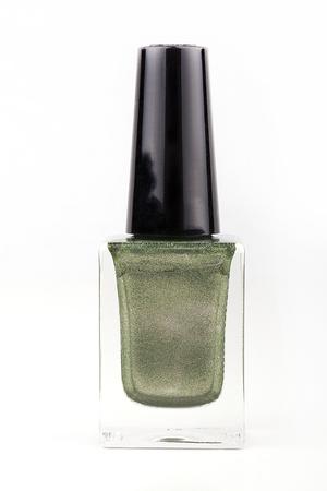 白い表面に緑のマニキュアボトル。白い背景に隔離された緑のマニキュア。