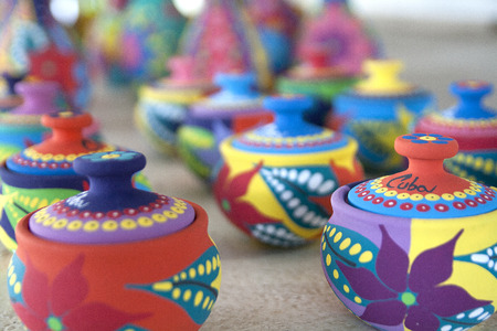Colorful pottery in a cuban market. Close up on first row, the rest fading in a blur. Imagens