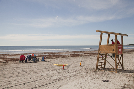 Lifeguard tower and swimmers on York beach, USA. Stock Photo