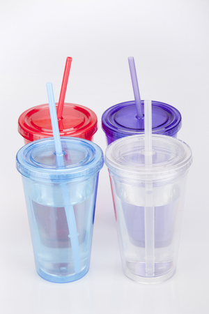 Colorful plastic tumbler glasses with lid and straw on a white surface. Travel cups isolated on white background.