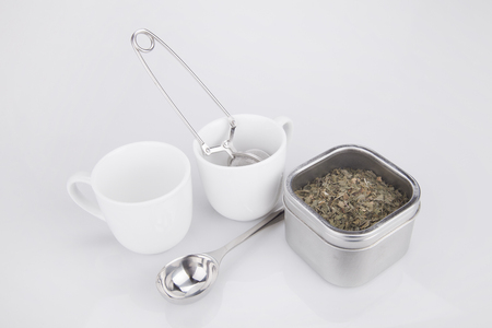 loose leaf: Tea leaves and accessories on a white surface. Tea kit isolated on white background.