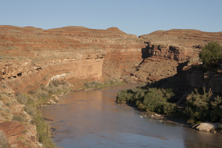 Beautiful red rock monument with river going through in San Juan, Utah, USA.