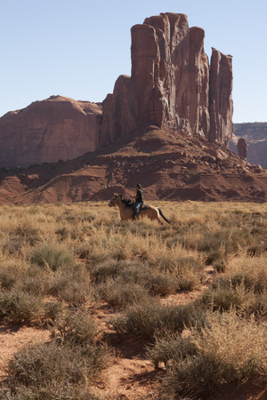 Navajo indian riding a horse in the desert of Monument Valley, UtahArizona, USA.