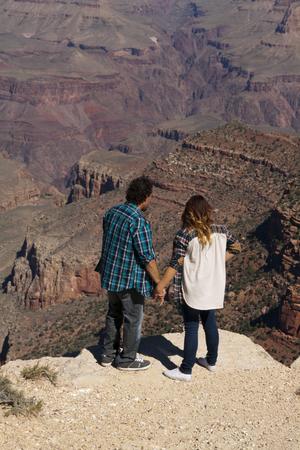 グランドキャニオン国立公園、アリゾナ州、米国で崖の端で手を繋いでいるカップル。 写真素材 - 84790310