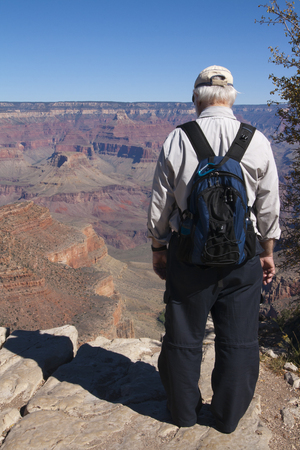 Senior man standing at the edge of a cliff at the Grand Canyon National Park; Arizona, USA. Imagens - 84790317