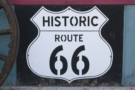 Historic route 66 sign on a vintage background with a wagon wheel in Arizona, USA.