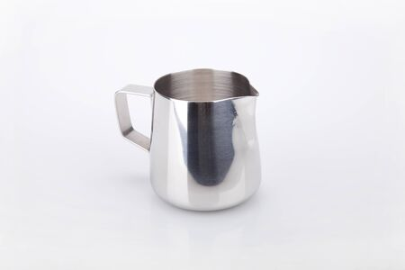 Stainless steel milk pitcher for cappuccinos on a white surface. Stainless pitcher isolated on white.