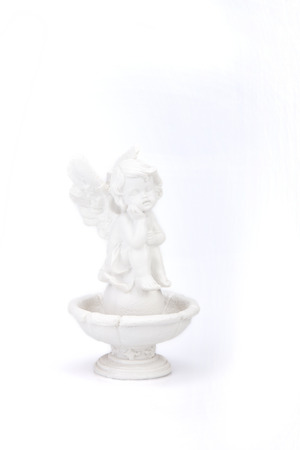 Statue of an angel sitting on a fountain on a white surface. Angel statue isolated on white background. Imagens
