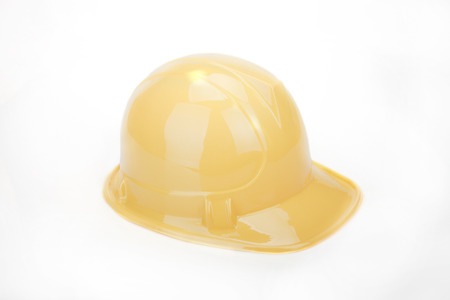 Yellow safety helmet on a white surface. Yellow hard hat isolated on white.