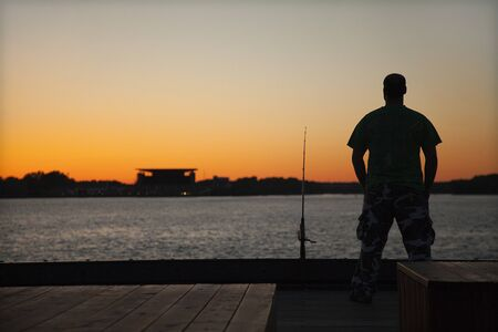 Fisherman with fishing rod on the dock by the river at sunset 写真素材