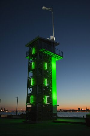 Green beacon against a twilight sky during sunset