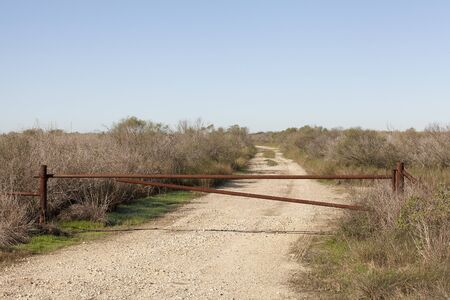 Gate at the entrance of a dirt road to an oil rigs field in Galveston, Texas, United States of America.