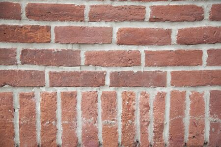 View of an old red brick wall with rich colorful grainy texture and details. Textured abstract background.