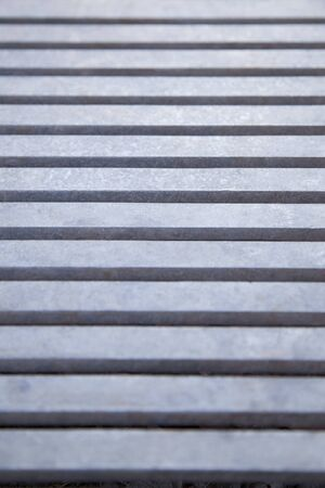 Close up view of a blueish metal grate. Steel grid. Frame filled with horizontal lines. Textured abstract background.