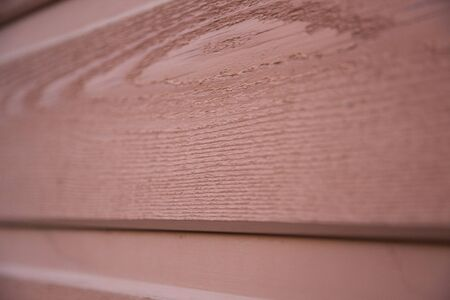 Close up view of a red grainy wood house plank. Textured abstract background.