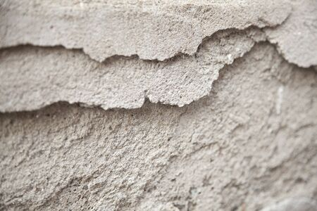 Gritty cement texture with some of it chipped off.  Broken concrete. Textured abstract background.