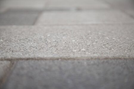 Narrow view of a concrete tile in the blurred sidewalk. Cement block on a pedestrian crossing. Textured abstract background bokeh.