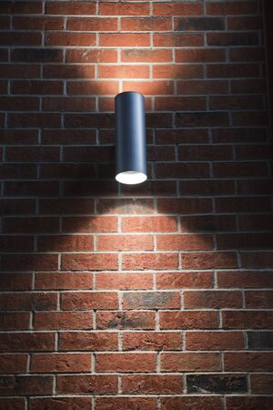 Single metal lamp illuminating a blank red brick wall. Gray metal light illuminating a wall upward and downward. Imagens