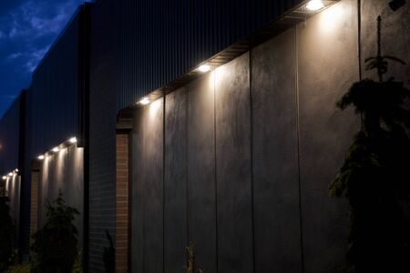Large pot lights illuminating a concrete wall with bricks at twilight. Illuminated blank building wall in the dark.