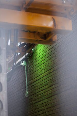 Yellow hoist and green LED light on a brown brick wall. Yellow painted beams of electric driven structure. Green LED light illuminating a brown brick wall.