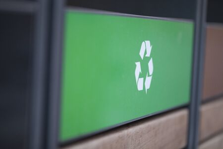 Recycling logo on a green panel shot at an angle. Recycling logo at an angle perspective. Shallow depth of field. Imagens