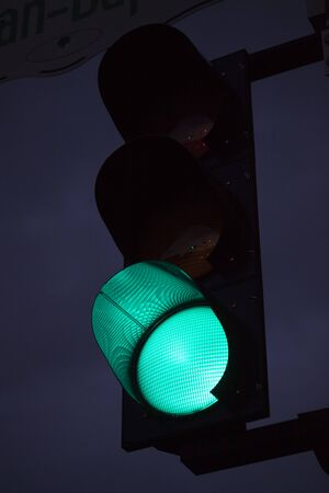 Green traffic light against the sky at twilight. Green light is on at a traffic light pole in the evening.