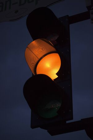 Yellow traffic light against the sky at twilight. Yellow light is on at a traffic light pole in the evening.