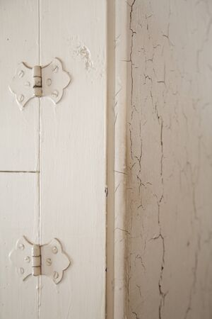 Old door hinges and cracking white paint on an antique furniture. Corner of an ancient dresser with paint cracking and peeling.