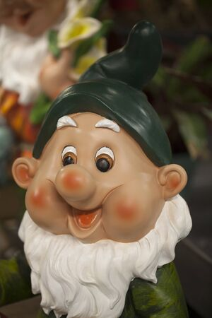 Cute dwarf living in a garden. Smiling garden gnome decoration against a blurry background. Funny elf in the garden. Happy dwarf figurine. Imagens