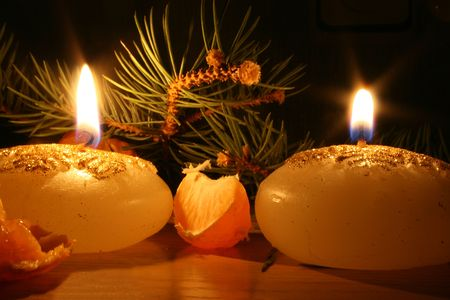 Two candles in the dark with new year tree on the background and mandarines
