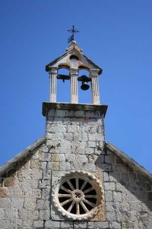 Church bell tower with one bell and rosette from the outside photo